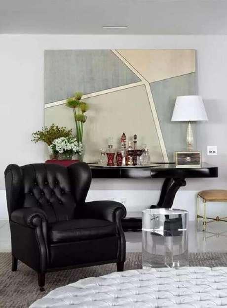 3. Sala sofisticada decorada com quadro grande e poltrona de couro preta antiga – Foto: Pinterest