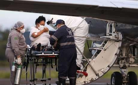 Funcionário do setor de saúde ajuda paciente de Covid-19 em Manaus a embarcar em avião do Exército em direção ao Maranhão. 15/1/2021. REUTERS/Bruno Kelly