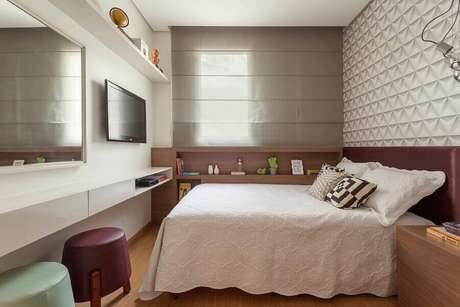 27. Decoração com puff colorido para quarto de casal planejado com papel de parede 3D – Foto: AMIS Arquitetura & Design