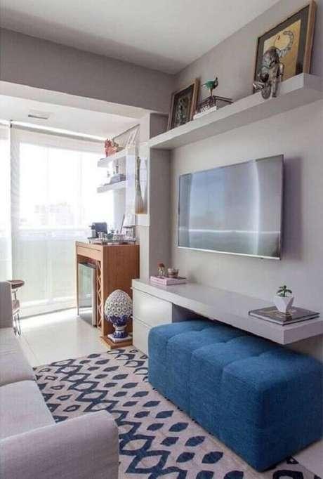 28. O puff colorido azul deu mais vida para a decoração da sala pequena em cinza claro – Foto: Jeito de Casa