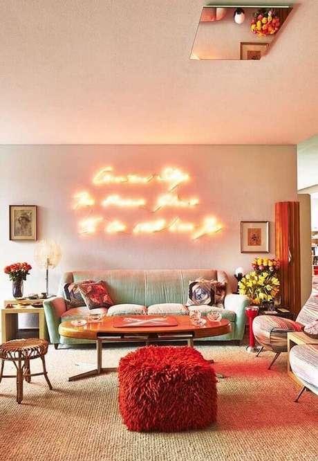 30. Decoração com puff colorido para sala com luminária neon – Foto: Decorholic