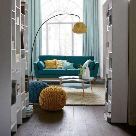 31. Puff colorido para sala de estar decorada com sofá retrô e tapete de crochê bege – Foto: