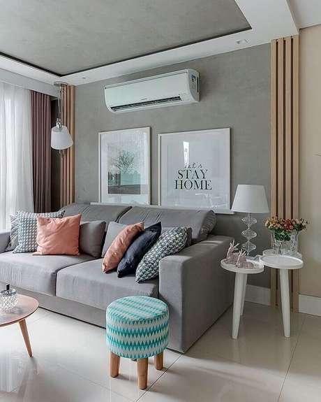 35. Puff colorido para sala cinza decorada com várias almofadas e mesa lateral branca – Foto: Pinterest