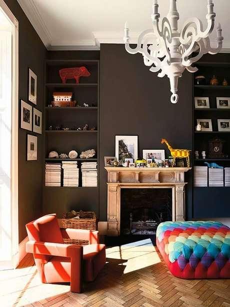 36. Decoração de sala preta com poltrona laranja e puff colorido – Foto: Larissa Carbone Arquitetura