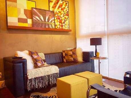 38. Puff quadrado colorido para sala de estar decorada com quadros abstratos e sofá marrom escuro – Foto: Andreas Móveis