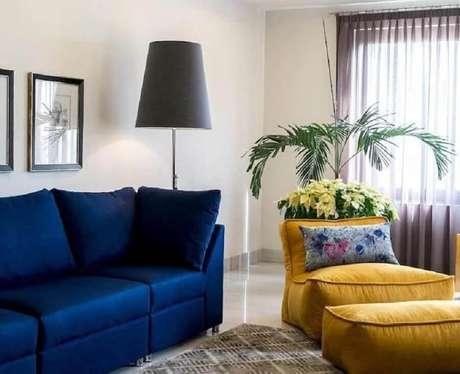 41. Decoração de sala de estar com puffo fofão colorido e sofá azul escuro – Foto: Pinterest