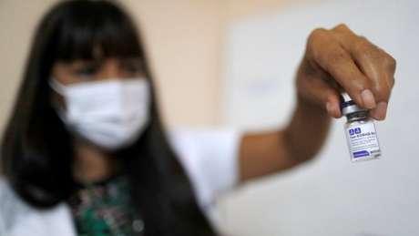 Um agente de saúde mostra a vacina russa que é fornecida na Argentina
