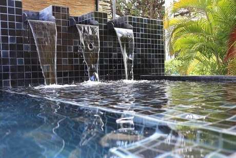 67- A piscina com cascata tem revestimento cerâmico na cor azul. Fonte: Tua Casa