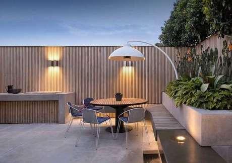 7. Arandela de madeira externa decora a área de lazer pequena. Fonte: Pinterest