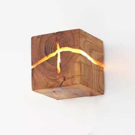 16. Arandela de madeira rústica com ranhuras que permitem a passagem da luz. Fonte: Pinterest