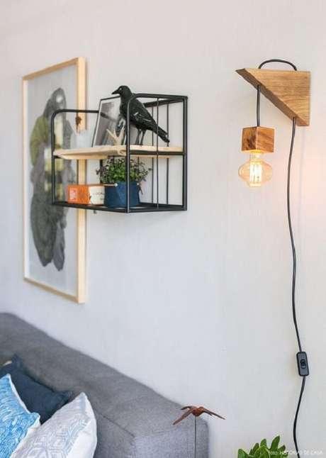 4. Arandela rústica de madeira traz um ponto de luz para a sala de estar. Fonte: História de Casa