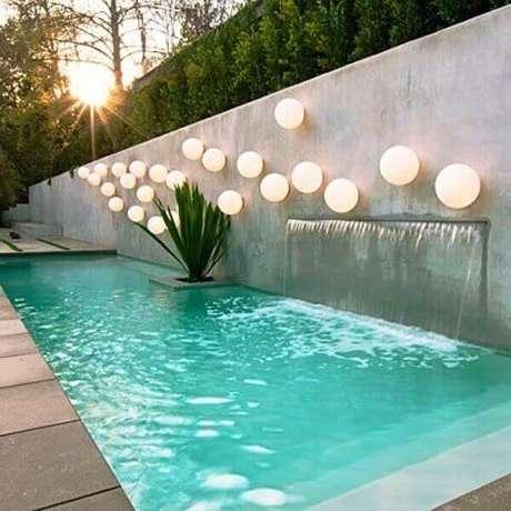 70- A cascata de piscina foi embutida no muro e tem varias luminárias completando a decoração. Fonte: Pinterest