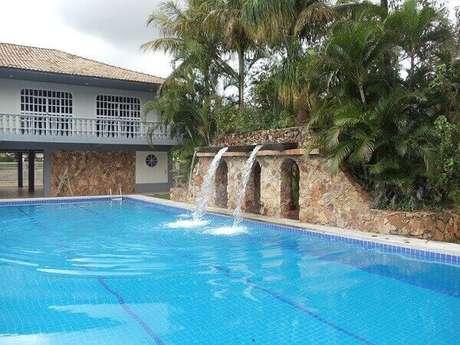 20- A cascata para piscina é formada por três saídas de água no alto da estrutura revestida de pedras naturais. Fonte: DF Imóveis