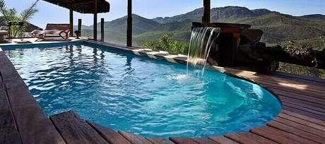 42- O acabamento da cascata para piscina é realizada com pedras e madeira. Fonte: Pinterest