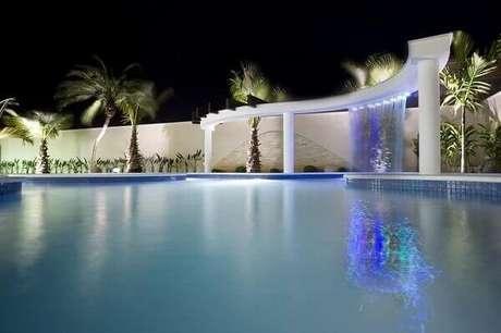 30- A cascata para piscina instalada na estrutura de alvenaria com linhas curvas tem iluminação com led. Fonte: Tua Casa
