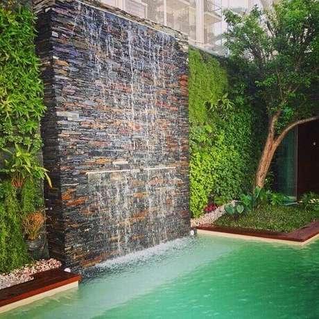 46- A cascata para piscina em parede de pedra tem duas saídas de água com alturas diferentes. Fonte : Pinterest