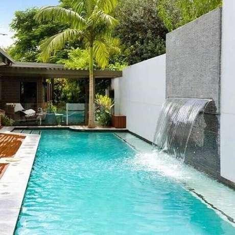 53- A parede com pastilhas cinza tem cascata para piscina embutida. Fonte: Cooperativa das Piscinas