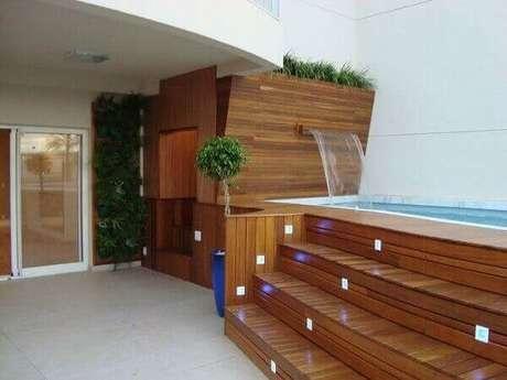 17- A cascata da piscina elevada tem a saída de água na parede revestida de madeira. Fonte: Pinterest