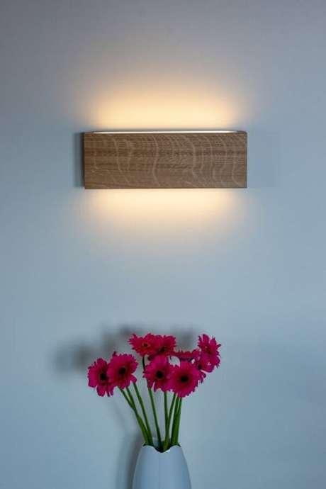 22. Decoração aconchegante com arandela de madeira. Fonte: Pinterest