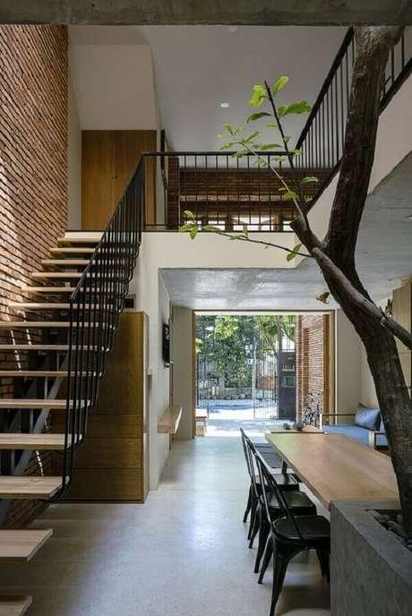 10. A árvore é o grande destaque dessa casa com mezanino interno. Fonte: ArchDaily