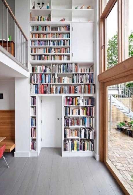 50. O espaço disponível para organização de objetos e livros se estende por toda a parede da casa com mezanino interno. Fonte: Pinterest