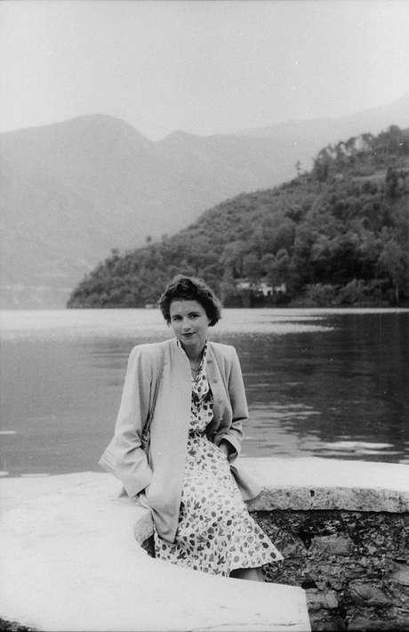 Mulher posa ao lado de lago