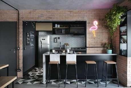 9. Decoração de cozinha americana estilo industrial com parede de tijolinho e luminária neon em formato de flamingo – Foto: Apartment Therapy