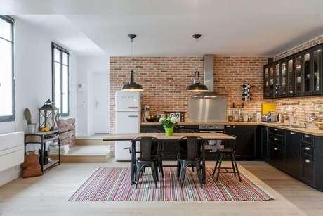 43. Parede de tijolinho e tapete listrado para decoração de cozinha estilo industrial ampla com armários pretos – Foto: Houzz