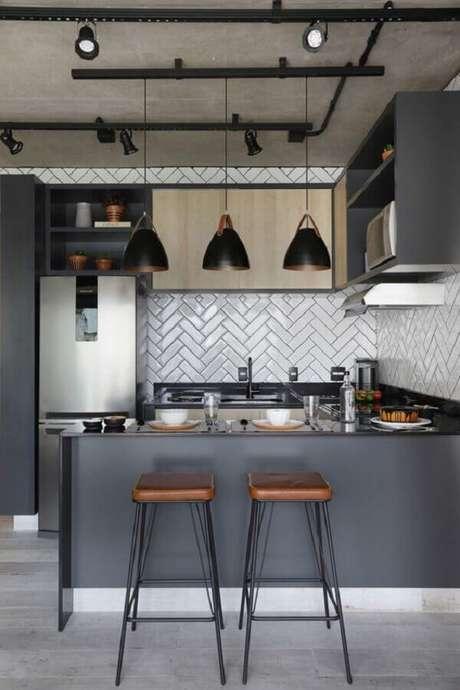 8. Cozinha americana estilo industrial toda cinza decorada com banquetas de couro e luminária pendente preta para a bancada – Foto: Mariana Orsi