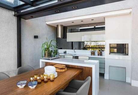 33. Revestimento para área gourmet com mesa de madeira e bancada de pedra – Via: Leonardo Muller