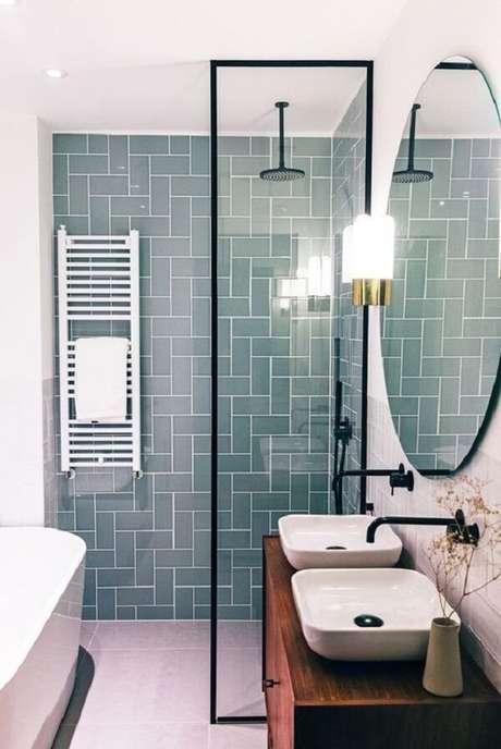 46. Bancada de madeira escura, cuba de apoio para banheiro branca e elementos em preto reforçam o estilo industrial. Fonte: Revista Viva Decora