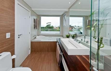 45. Bancada de madeira extensa acomoda uma linda e cuba de apoio para banheiro branca. Projeto por Juliana Pippi