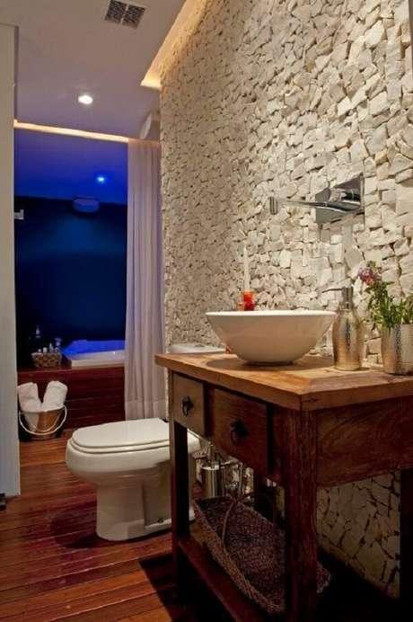 19. O aparador de madeira serve de base para a cuba de apoio para banheiro oval. Projeto por Gabriel Magalhães e Luiz Claudio Souza Arquitetos