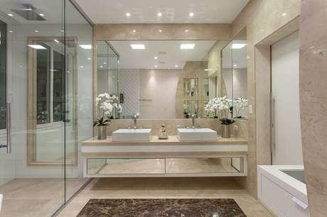 11. O apoio para cuba de banheiro com estrutura espelhada traz elegância ao espaço. Projeto por Iara Kilaris