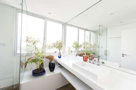 16. Os móveis em marcenaria branca se misturam com a cuba de apoio para banheiro. Projeto por Cláudia Lima