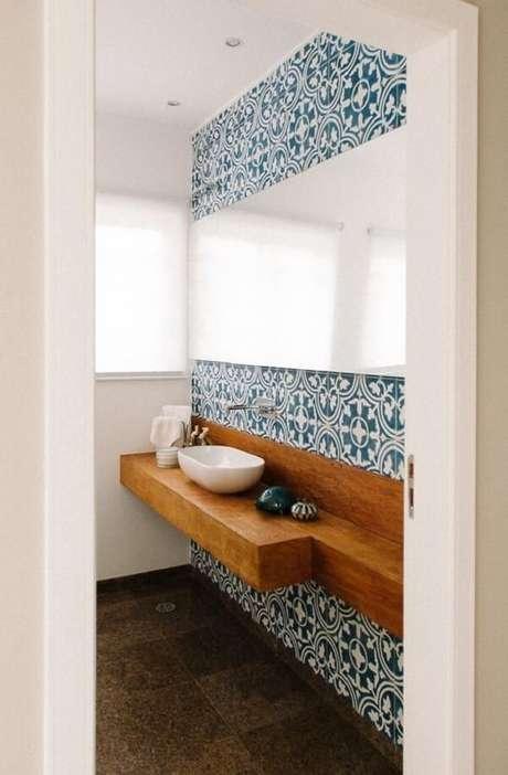 13. Parede com ladrilho azul e bancada de madeira com cuba de apoio para banheiro formam uma combinação harmoniosa. Projeto por Codecorar