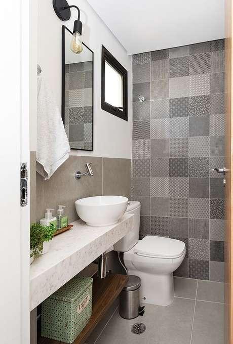 12. Parede com ladrilho hidráulico cinza e cuba de apoio para banheiro decoram o espaço. Projeto por PAGAMA Arquitetura + Design