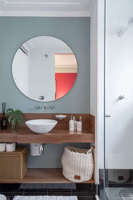 9. Parede com pintura cinza se conecta com a bancada em madeira e a cuba de apoio oval para banheiro branca. Projeto por Batistelli Arquitetura e Design