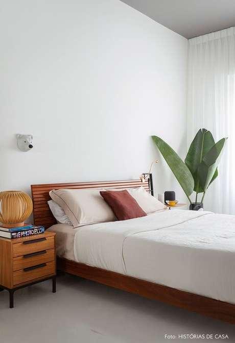 40. Cama de madeira no quarto clean decorado com plantas – Via: Histórias de Casa