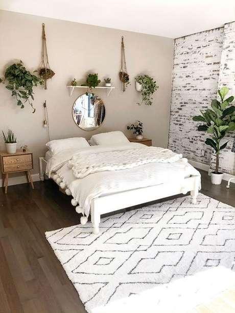 21. Cama de madeira branca no quarto cheio de plantas – via: Pinterest