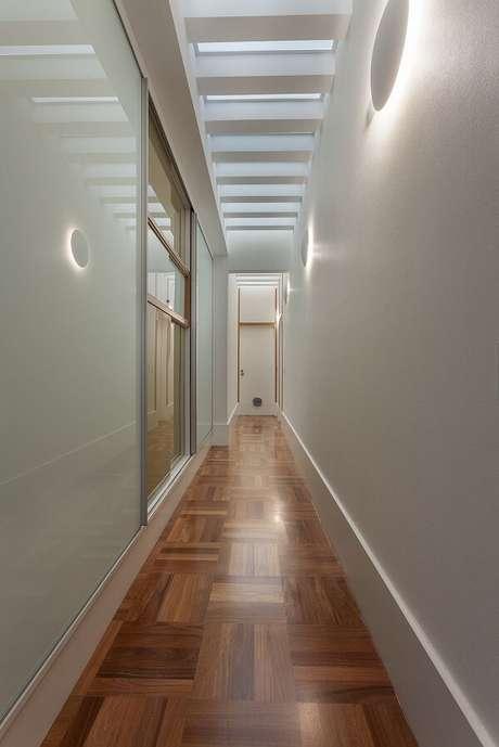4. A luminária de parede para corredor metálicas brancas trazem pontos de luz ao ambiente. Projeto por Aline Cobra Design e Arquitetura