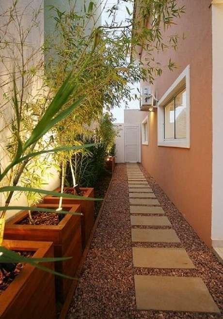 12. A luminária para corredor externo combinada a vegetação traz um charme para o espaço. Fonte: Casa Decorada