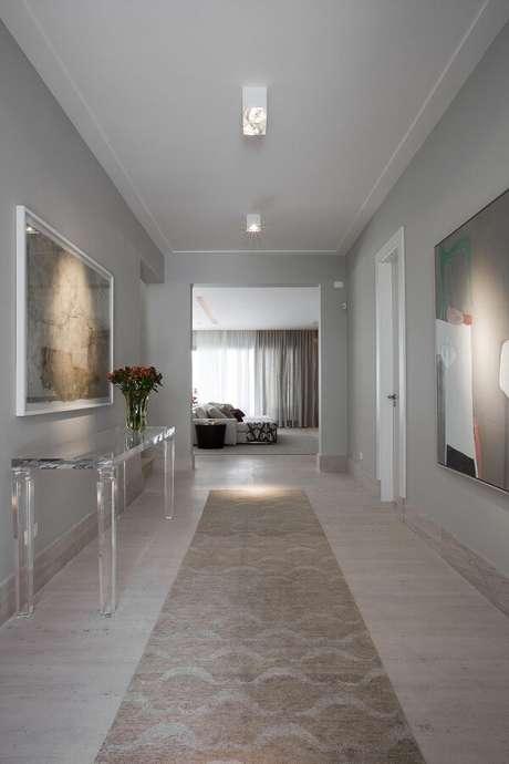 16. A luminária para corredor interno branca se conecta com o aparador acrílico e o tapete com estampa neutra. Projeto por Marília Veiga Interiores