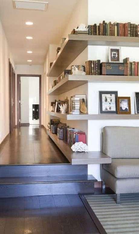 18. A luminária para corredor interno embutida no teto realça a presença das prateleiras de concreto que contornam a parede. Fonte: Pinterest