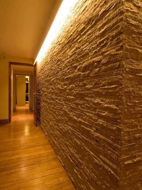 5. A luminária para corredor pequeno ilumina a área de passagem e realça a parede revestida com pedra canjiquinha. Projeto por BPA Arquitetura