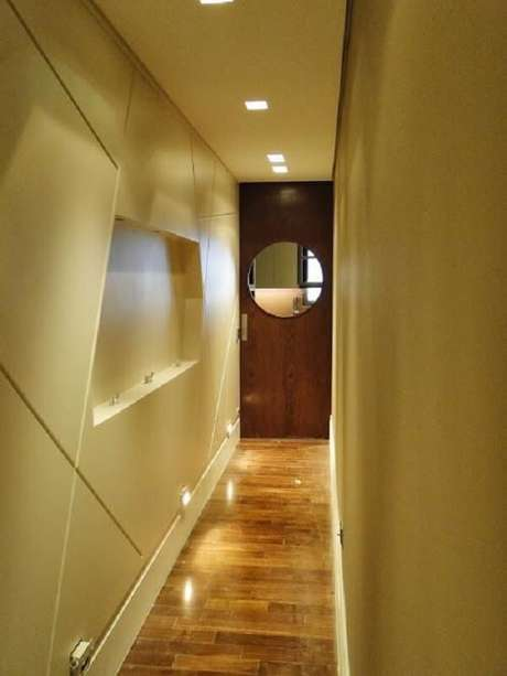 24. Além da luminária para corredor pequeno no teto é possível perceber a presença de luminária de parede para corredor. Projeto por Debora Nanni