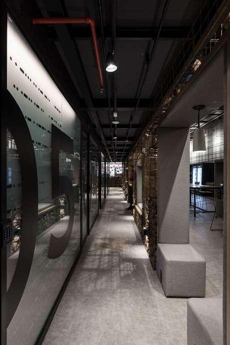 25. Ambiente com tubulação aparente e luminária para corredor interno trilho em tom preto decoram o espaço. Projeto por MOV.IN Arquitetos