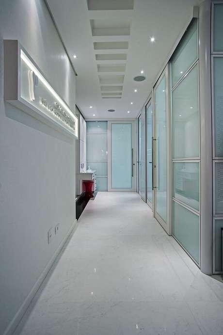 29. Corredor com portas de vidro e pontos e luminária para corredor embutida no teto discreta. Projeto por Patrícia Azoni