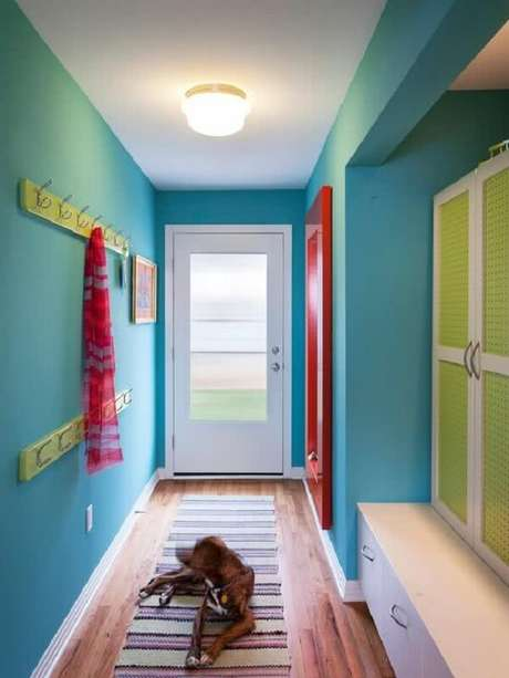 39. Modelo de luminária para corredor interno com parede azul e decoração vermelha e verde. Fonte: Pinterest