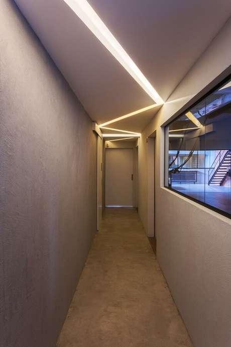 45. Parede com pintura cinza e luminária para corredor interno embutida forma um lindo recorte iluminado no teto. Fonte: Angatu